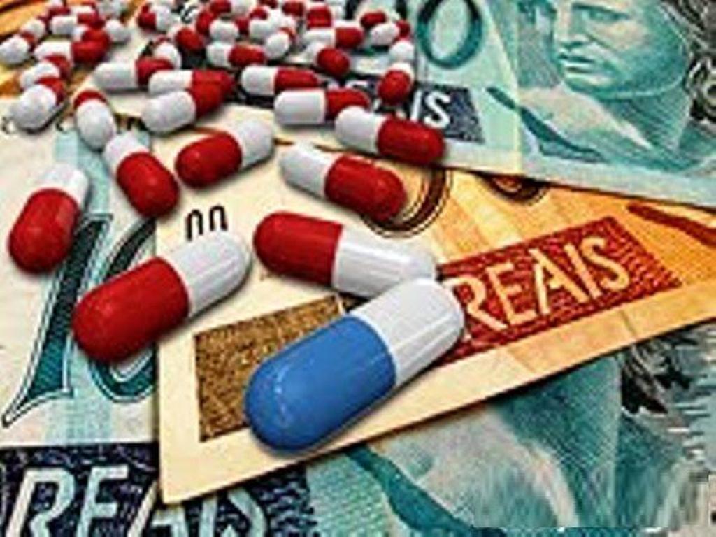 varias pilulas de remédio em cima de notas de reais